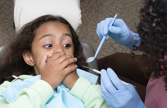 Girl covering her mouth because she is afraid of the dentist